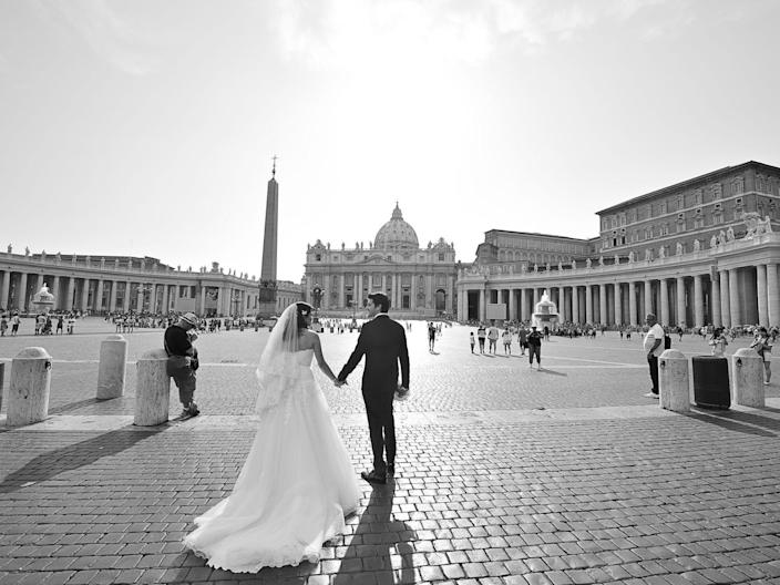 A bride and groom hold hands as they walk through a cobblestone street in Rome, Italy.