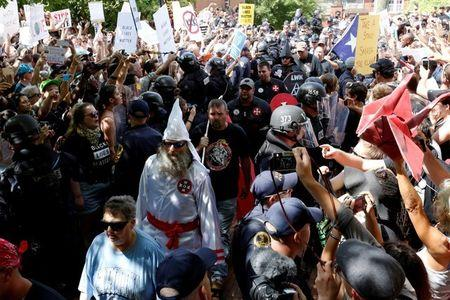 FILE PHOTO: Riot police protect members of the Ku Klux Klan from counter-protesters as they arrive to rally in opposition to city proposals to remove or make changes to Confederate monuments in Charlottesville, Virginia, U.S., July 8, 2017. REUTERS/Jonathan Ernst/File Photo