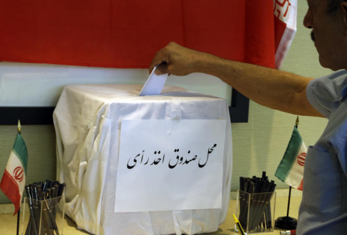 A man places his ballot in a box as Iranians outside their country of origin cast ballots in Iran's presidential election, in a hotel meeting room in Los Angeles Friday, June 14, 2013. Iranian-Americans and expatriates cast ballots Friday in polling places across the United States, joining their countrymen half a world away in selecting the next Iranian president (AP Photo/Reed Saxon)