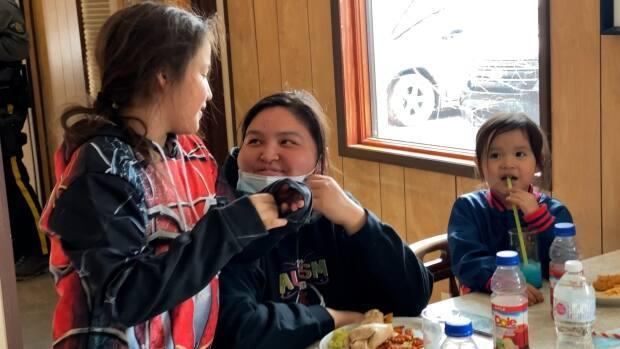 Carla Norwegian, centre, eats lunch with her three kids at the Snowshoe Cafe. Their family lost everything in the flood.