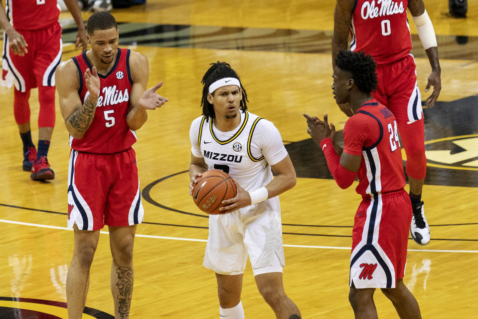 Mississippi's Jarkel Joiner, right, and KJ Buffen, left, celebrate after Missouri's Drew Buggs, center, was called for traveling during the first half of an NCAA college basketball game Tuesday, Feb. 23, 2021, in Columbia, Mo. (AP Photo/L.G. Patterson)