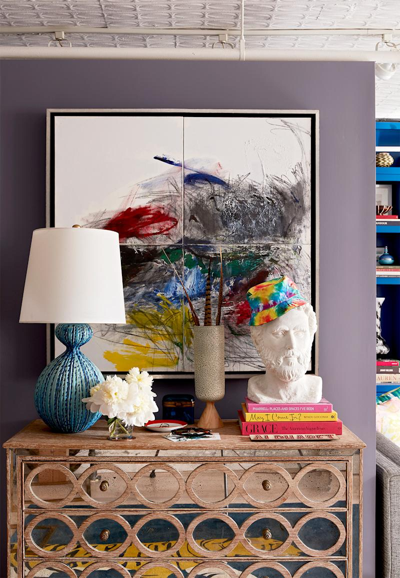 mirrored accent table under abstract artwork