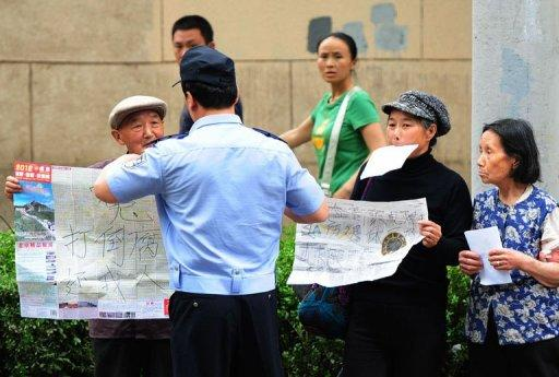 Elderly petitioners protesting about medical and land grab issues are detained by police outside the Chaoyang Hospital where blind Chinese activist Chen Guangcheng is being held, in Beijing on May 9, 2012