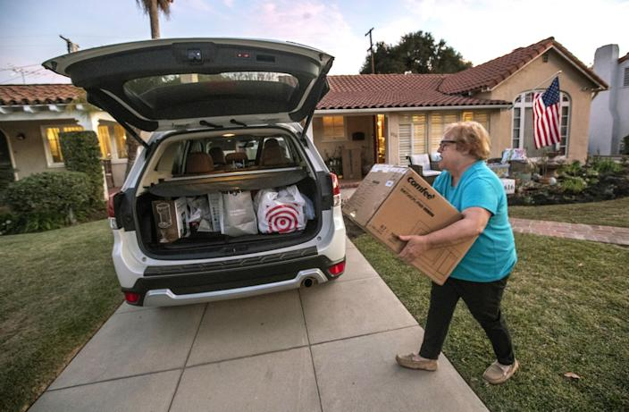 Jo Anne Kindler loads a box containing a microwave oven into the back of her car, a day before driving to her new home