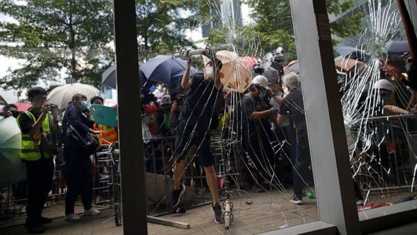 PHOTO: A protester tries to break the glass to get into the Legislative Council in Hong Kong Monday, July 1, 2019. (Jeff Cheng/HK01 via AP)