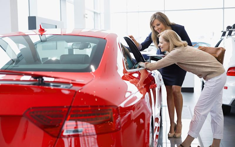 Saleswoman and woman looking at car in showroom - Hero Images/Alamy