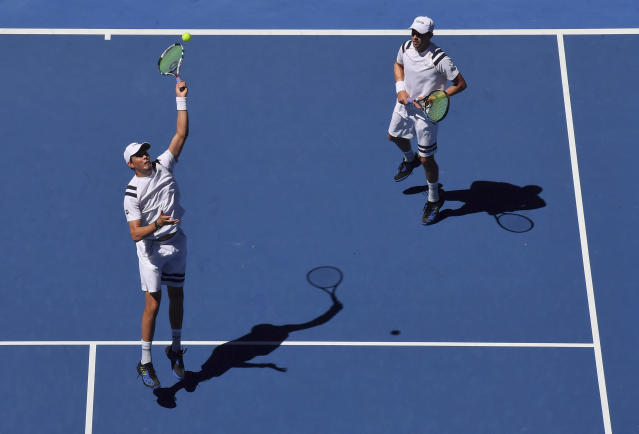 FILE - In this Jan. 19, 2018 file photo, United States' Bob and Mike Bryan play in the men's doubles second round match against Max Mirnyi of Belarus and Austria's Phillip Oswald at the Australian Open tennis championships in Melbourne, Australia.The Bryan brothers have reunited as a doubles combination at a Grand Slam tournament and have opened with a 7-6 (4), 7-6 (1) win over Alex Bolt and Marc Polmans at the Australian Open in Melbourne, Australia, Wednesday Jan. 16, 2019. (AP Photo/Andy Brownbill,File)