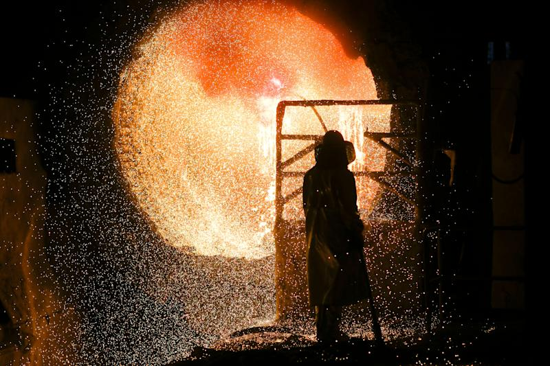 An employee in protective clothing maintains at steel pouring ladle during a guided media tour at the steel producer Salzgitter AG in Salzgitter, March 5, 2019. (Photo: Markus Schreiber/AP)