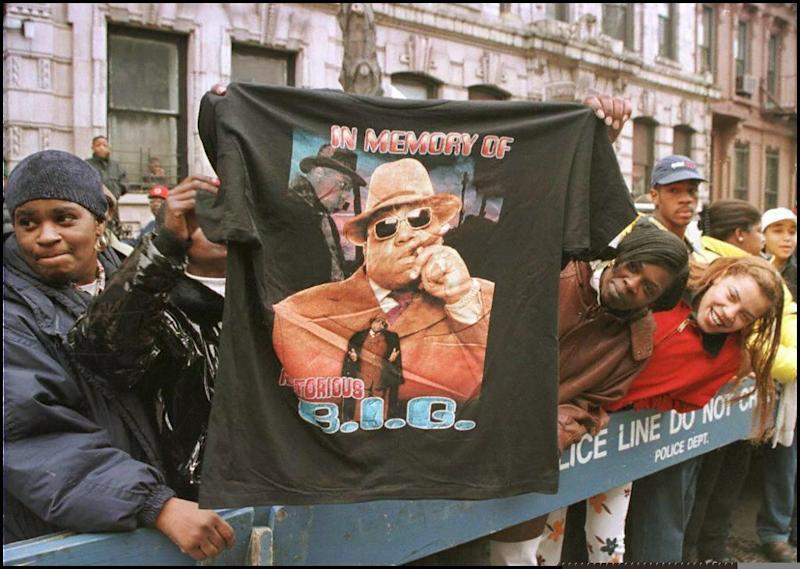 A man displays a T-shirt tribute to rapper Biggie Smalls as friends and fans lined the funeral procession route through his old neighborhood in Brooklyn, in this March 19, 1997 file photo