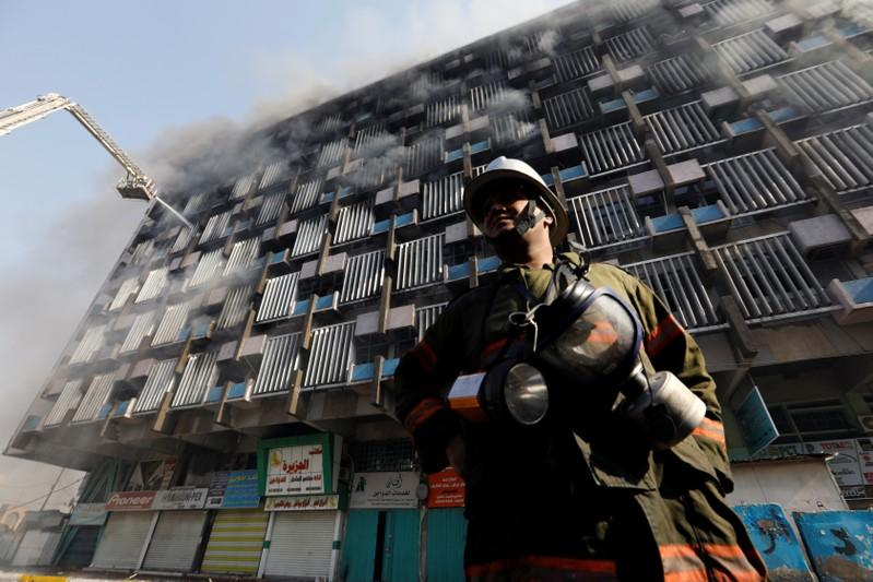 A fireman is seen as firemen hose down a burning building in Baghdad