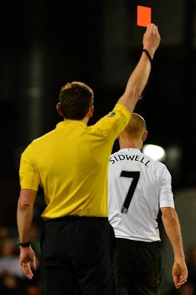 Fulham midfielder Steve Sidwell (R) receives a red card after tackling QPR defender Armand Traore during their Premier League match in London on April 1, 2013. Referee Lee Probert brandished a straight red card after Sidwell lunged in on Traore in the 79th minute