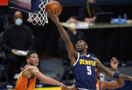 Denver Nuggets guard Will Barton drives for a basket past Phoenix Suns guards Devin Booker, back left, and Chris Paul during the second half of an NBA basketball game Friday, Jan. 1, 2021, in Denver. The Suns won 106-103. (AP Photo/David Zalubowski)