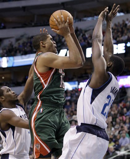 Dallas Mavericks guard Rodrigue Beaubois, left, of Guadeloupe, and center Ian Mahinmi of France, right, defend against a shot attempt by Milwaukee Bucks forward Tobias Harris, center, in the first half of an NBA basketball game Friday, Jan. 13, 2012, in Dallas. (AP Photo/Tony Gutierrez)