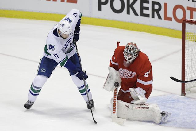 Detroit Red Wings goalie Jonas Gustavsson (50) of Sweden deflects a shot by Vancouver Canucks center Ryan Kesler (17) during the first period of an NHL hockey game in Detroit, Monday, Feb. 3, 2014. (AP Photo/Carlos Osorio)