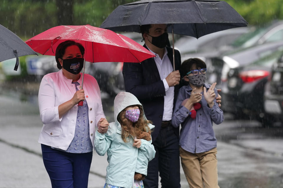 Democratic gubernatorial candidate, Virginia State Sen. Jennifer McClellan, left, arrives with her family, Samantha Mille, second from left, husband, Dave Mills and son Jackson Mills, right, at an early voting location in Richmond, Va., Saturday, May 29, 2021. McClellan faces four other Democrats in the primary. (AP Photo/Steve Helber)