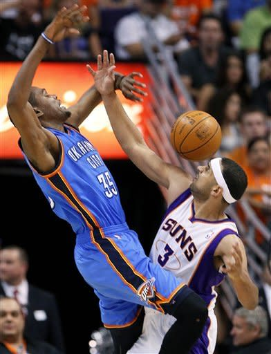 Oklahoma City Thunder forward Kevin Durant (35) has the ball knocked loose by Phoenix Suns forward Jared Dudley during the second half of an NBA basketball game, Wednesday, April 18, 2012, in Phoenix. (AP Photo/Matt York)