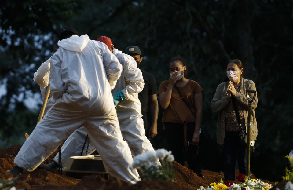 People mourn as a relative is buried by cemetery workers in protective gear as a preventive measure against the spread of the novel coronavirus disease, COVID-19, at the Vila Formosa cemetery in Sao Paulo, Brazil, on April 17, 2021. - The number of people who have died worldwide in the Covid-19 pandemic has surpassed three million. The worlds Covid-19 death toll surpassed three million on Saturday, according to Johns Hopkins University. (Photo by Miguel SCHINCARIOL / AFP) (Photo by MIGUEL SCHINCARIOL/AFP via Getty Images)