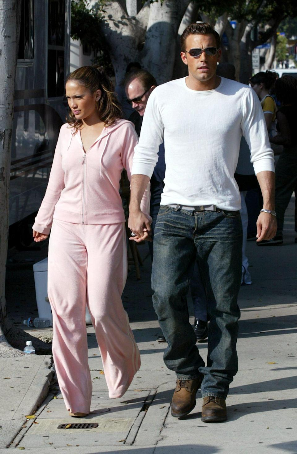 <p>On a stroll in Beverly Hills in October 2002, the couple are an early aughts mood, from the baby pink velour tracksuit to the baggy jeans and shades.</p>