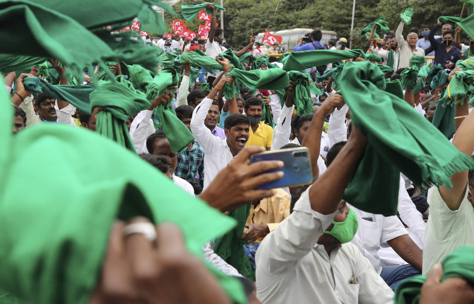 Indian farmers raise their shawls and shout anti-government slogans during a protest against farm bills in Bengaluru, India, Monday, Sept. 21, 2020. (AP Photo/Aijaz Rahi)
