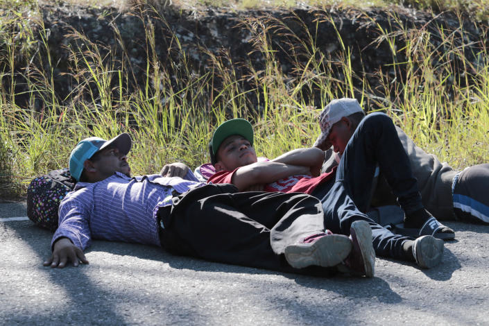 Migrants lie on the side of the road on their way North near Agua Caliente, close to the border with Guatemala, Thursday, Dec. 10, 2020. Honduran security forces stationed on the highway a few kilometers before Agua Caliente, asked the migrants for their passports or identity cards and proof of a COVID-19 test, and if they did not produce those documents they would not be allowed to move on. (AP Photo/Delmer Martinez)