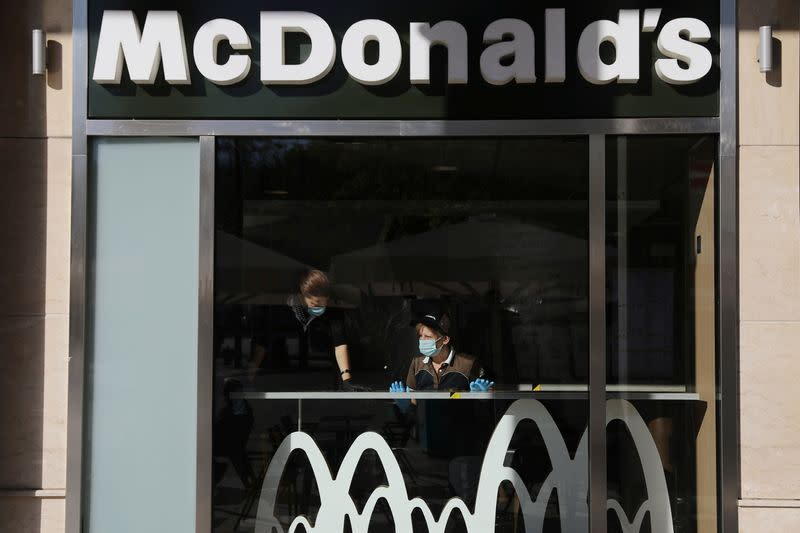 Cleaning ladies wearing protective face masks are seen inside a McDonald's restaurant, amid the spread of the coronavirus disease (COVID-19), in Athens