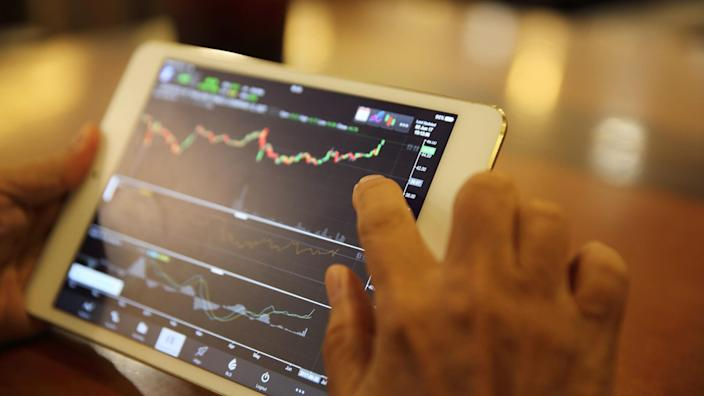 person using tablet to look at stock market