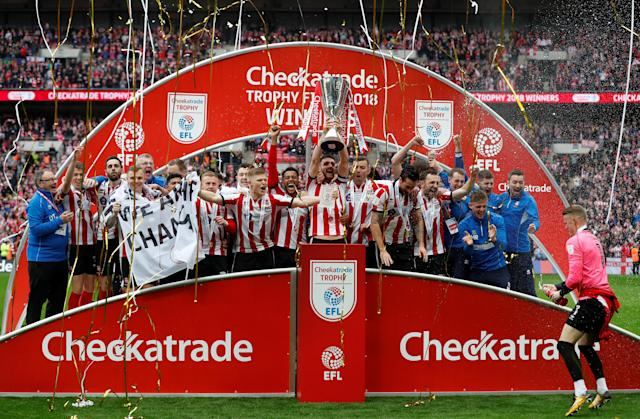 "Soccer Football - Checkatrade Trophy Final - Lincoln City vs Shrewsbury Town - Wembley Stadium, London, Britain - April 8, 2018 Lincoln City celebrate with the trophy after winning the Checkatrade Trophy Final Action Images/Matthew Childs EDITORIAL USE ONLY. No use with unauthorized audio, video, data, fixture lists, club/league logos or ""live"" services. Online in-match use limited to 75 images, no video emulation. No use in betting, games or single club/league/player publications. Please contact your account representative for further details."