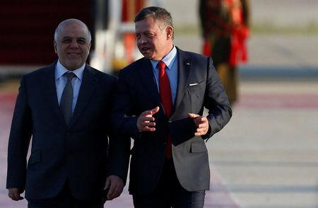 Jordan's King Abdullah II welcomes Iraqi Prime Minister Haider al-Abadi during a reception ceremony at the Queen Alia International Airport in Amman