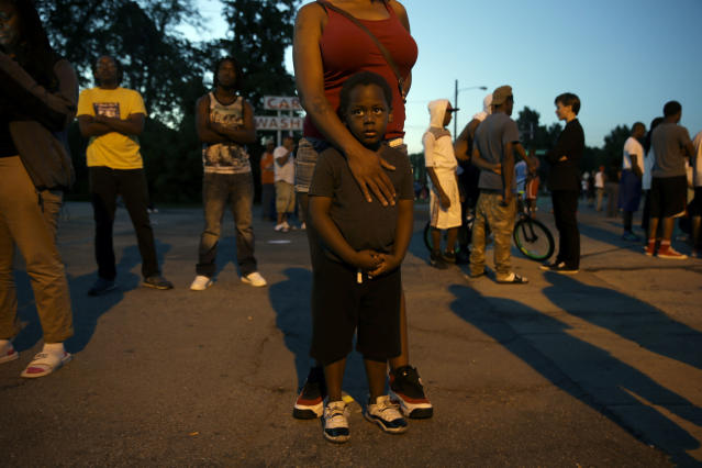 <p>Jeremiah Parker, 4, stands in front of his mother, Shatara Parker, as they attend a protest Wednesday, Aug. 13, 2014, in Ferguson, Mo. Nights of unrest have vied with calls for calm in a St. Louis suburb where Michael Brown, an unarmed black teenager was killed by police, while the community is still pressing for answers about the weekend shooting. (AP Photo/Jeff Roberson) </p>