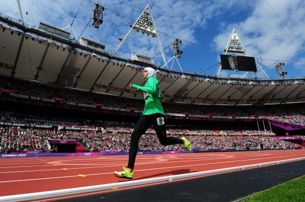 The 19-year-old, who wore a white head cover, a long sleeved green top and black leggings and sported luminous green running spikes, received a generous ovation from a capacity-crowd at the Olympic stadium as she trailed in last of the eight runners.