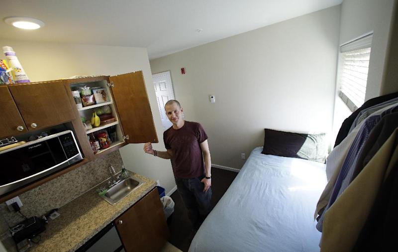 In this photo taken Wednesday, April 24, 2013, Kris King spreads stands in the kitchen, which is adjacent to the bed which is next to an open closet, in his tiny apartment in Seattle. Even King was initially shocked by the size of the apartment he rented near downtown, roughly the size of large parking spot. Cities such as San Francisco, New York and Boston have been encouraging tiny apartments to cater to young workers, retirees others who prefer city dwelling, singles or students. San Francisco last fall approved construction of apartments as small as 220 square feet, while Boston has approved 300 new units as small as 375 sq. feet. But in Seattle, where city codes have allowed for even smaller micro-apartments and dozens have been built in the last five years, the trend is facing a backlash from some neighbors who are pushing for a building moratorium or for them to be more adequately regulated. (AP Photo/Elaine Thompson)