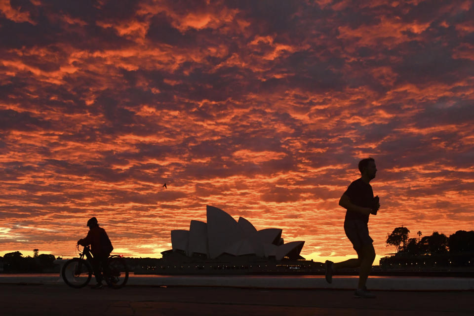 A jogger runs past the Sydney Opera House at dawn in Sydney, Wednesday, July 28, 2021. Australia's largest city Sydney will remain in lockdown for another four weeks due to a growing COVID-19 cluster. (Mick Tsikas/AAP Image via AP)