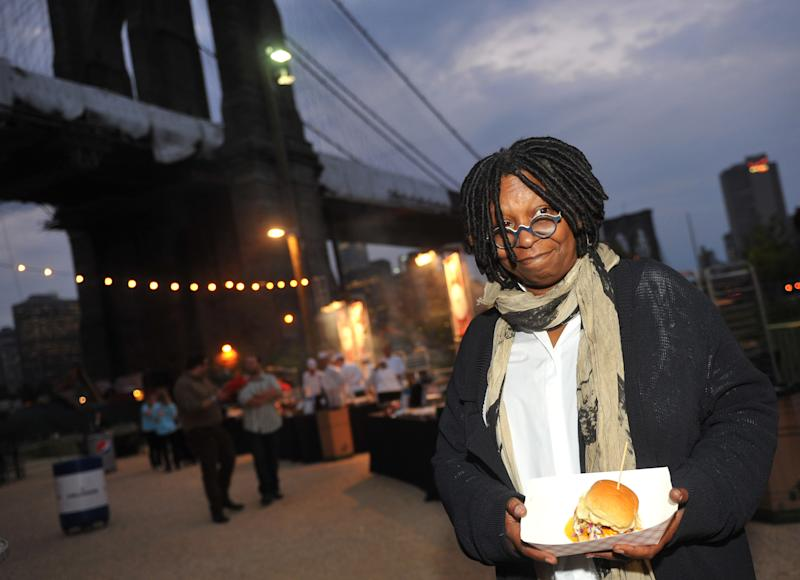 FILE - In this Sept. 30, 2012 file photo, Whoopi Goldberg poses with a burger at the New York City Wine and Food Festival's Burger Bash, in the Brooklyn borough of New York. Goldberg teams up in October 2012 with celebrity chef, Art Smith, with help on tunes from Questlove, to serve up a couple dozen inspired takes on one of America's favorite fried foods, chicken. The event is part of the fifth annual New York City Wine and Food Festival. (AP Photo/Diane Bondareff, File)