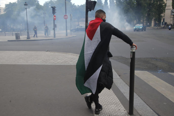 A demonstrator covered with a Palestinian flag stops at a street pole during a banned protest in support of Palestinians in the Gaza Strip, Saturday, May, 15, 2021 in Paris. Marches in support of Palestinians in the Gaza Strip were being held Saturday in a dozen French cities, but the focus was on Paris, where riot police got ready as organizers said they would defy a ban on the protest. (AP Photo/Michel Euler)