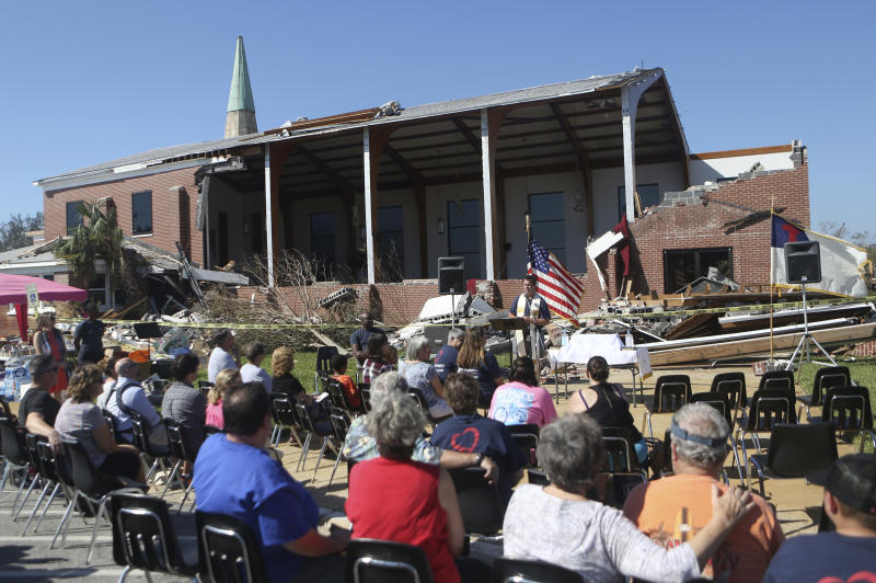 The Rev. John Blount leads a church service outside of St. Andrew United Methodist Church in Panama City, Florida on Sunday, Oct. 14, 2018. A small group gathered for the weekly Sunday service despite the substantial damage the church received during Hurricane Michael. [Patti Blake/Northwest Florida Daily News via AP)