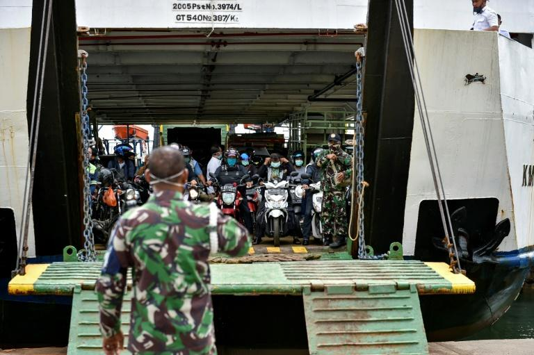 Indonesian soldiers watch as passengers prepare to drive off a ferry in the country's west -- the country is deploying a vast number of troops to enforce social-distancing guidelines