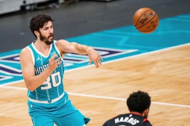 Charlotte Hornets guard Nate Darling passes the ball against the Toronto Raptors during the second half of an NBA basketball game in Charlotte, N.C., on Saturday. Darling became the first Nova Scotian to play in the NBA regular season. (AP Photo/Jacob Kupferman - image credit)