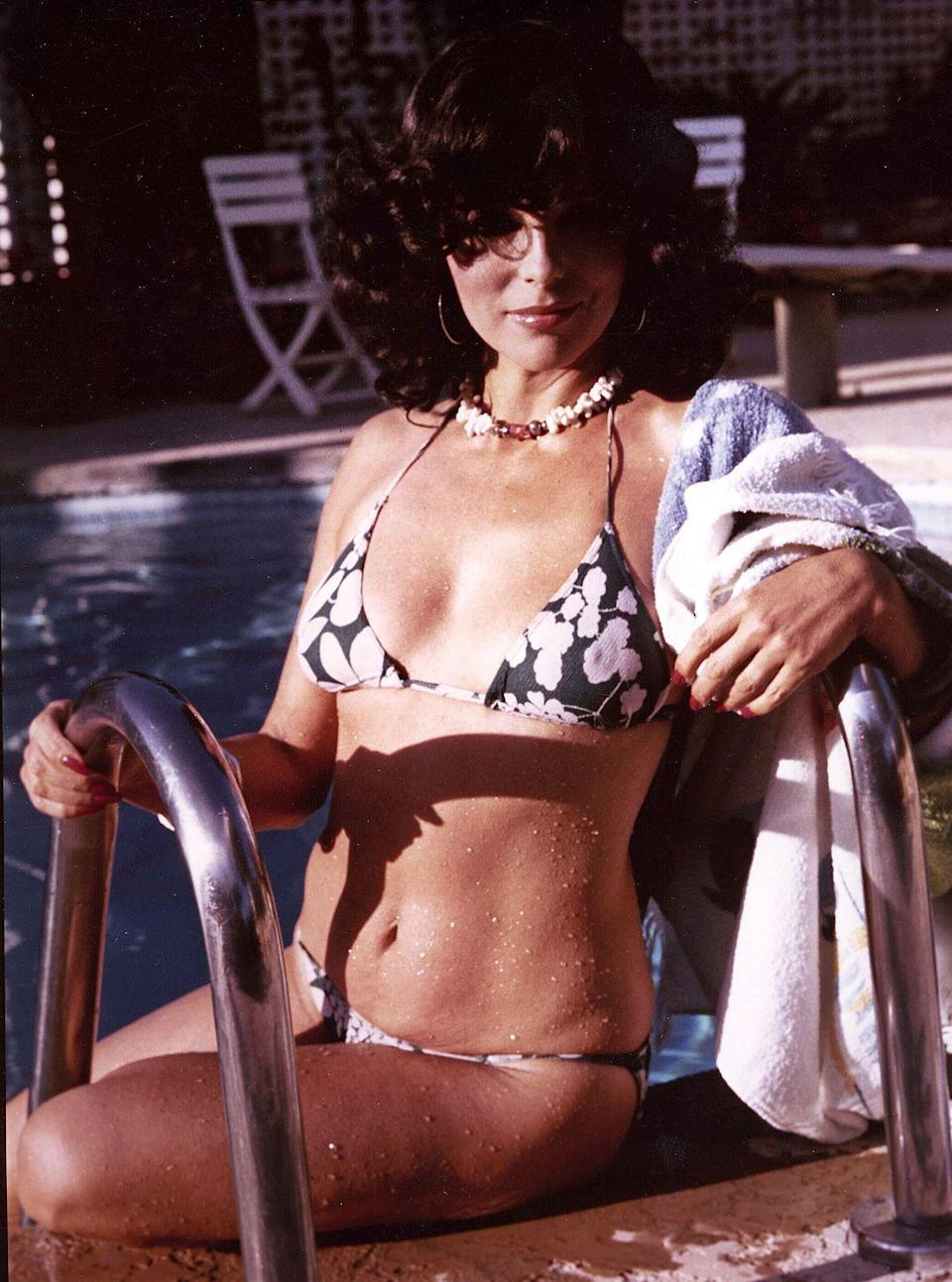 <p>Actress Joan Collins wears a floral bikini as she enjoys the pool in the backyard of her Beverly Hills home in 1976. </p>