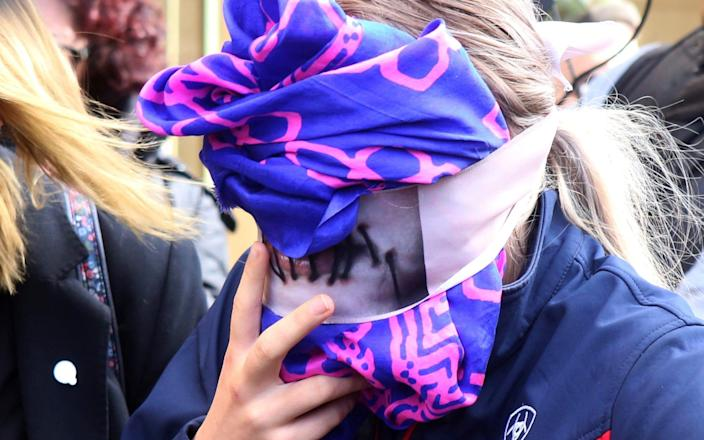 A 19-year old British woman, right, covers her face as she leaves from the Famagusta court after her trial - AP