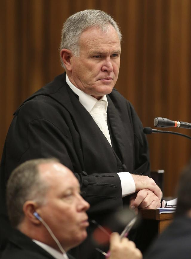 Defence attorney Barry Roux looks on as State prosecutor Gerrie Nel (not pictured) cross-examines South African Olympic and Paralympic sprinter Oscar Pistorius during his trial at the North Gauteng High Court in Pretoria April 9, 2014. Nel forced Oscar Pistorius on Wednesday to look at a forensic photograph of the head of his girlfriend Reeva Steenkamp after it was destroyed by a gunshot fired by the Olympic and Paralympic track star. REUTERS/Siphiwe Sibeko (SOUTH AFRICA - Tags: SPORT ATHLETICS CRIME LAW)