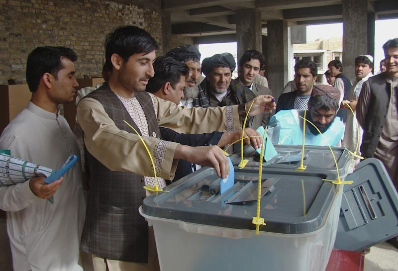 Afghan men line up to cast their votes at a polling station in Lashkargah, capital of Helmand province, Afghanistan, Saturday, April 5, 2014. Afghans flocked to polling stations nationwide on Saturday, defying a threat of violence by the Taliban to cast ballots in what promises to be the nation's first democratic transfer of power. The turnout was so high that some polling centers ran out of ballots. (AP Photo/Abdul Khaliq)