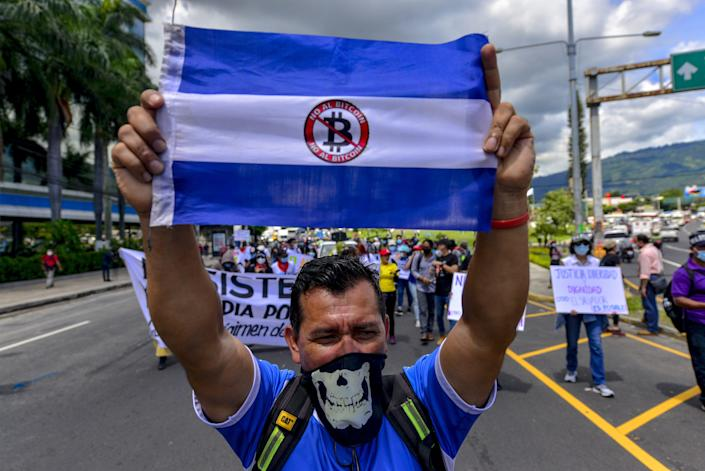 A man holds a blue and white flag over his head.