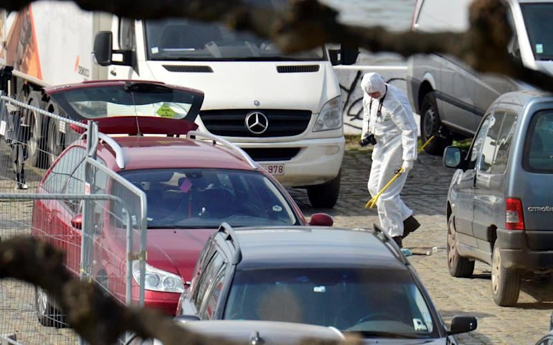 A forensics expert stands next to the car stopped by police in Antwerp - Credit: Reuters