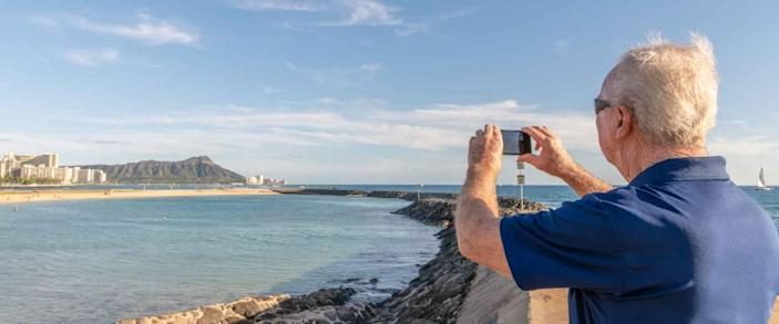 A senior man takes a photo of Diamond Head while on a family trip to Honolulu, Hawaii.