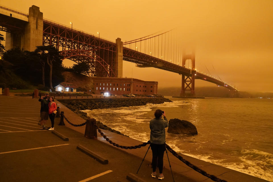 FILE - In this Sept. 9, 2020, file photo, taken at 11:25 a.m. people stop near Fort Point to take pictures of an orange sky over the Golden Gate Bridge caused by heavy smoke from wildfires in San Francisco. Wildfires that scorched huge swaths of the West Coast churned out massive plumes of choking smoke that blanketed millions of people with hazardous pollution that spiked emergency room visits and that experts say could continue generating health problems for years. An Associated Press analysis of air quality data shows 5.2 million people in five states were hit with hazardous levels of pollution for at least a day. (AP Photo/Eric Risberg, File)
