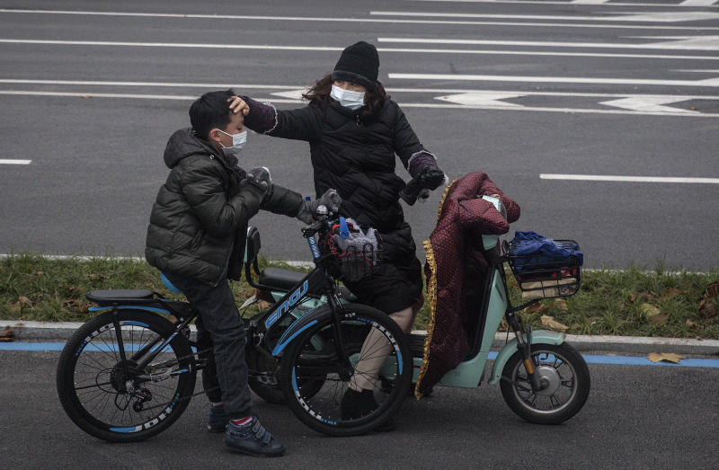 WUHAN, CHINA - JANUARY 27: (CHINA-OUT) A woman checks her son's forehead on January 27, 2020 in Wuhan, China. As the death toll from the coronavirus reaches 80 in China with over 2700 confirmed cases, the city remains on lockdown for a fourth day. (Photo by Getty Images)