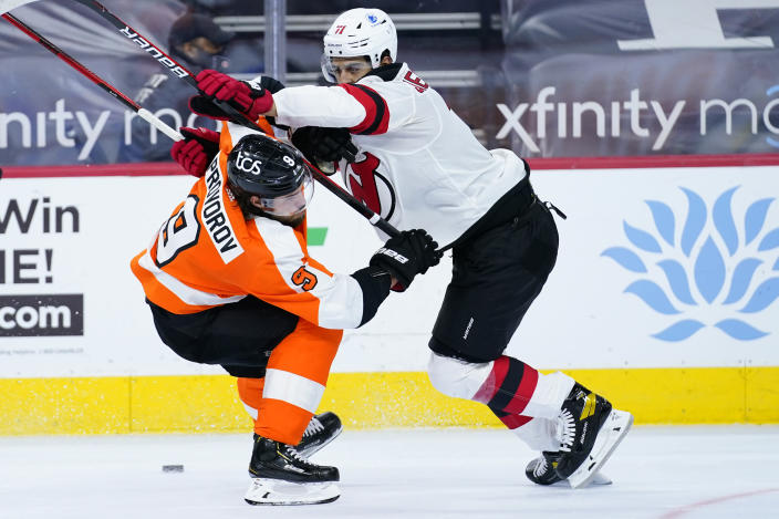 Philadelphia Flyers' Ivan Provorov, left, and New Jersey Devils' Jonas Siegenthaler battle for the puck during the second period of an NHL hockey game, Monday, May 10, 2021, in Philadelphia. (AP Photo/Matt Slocum)