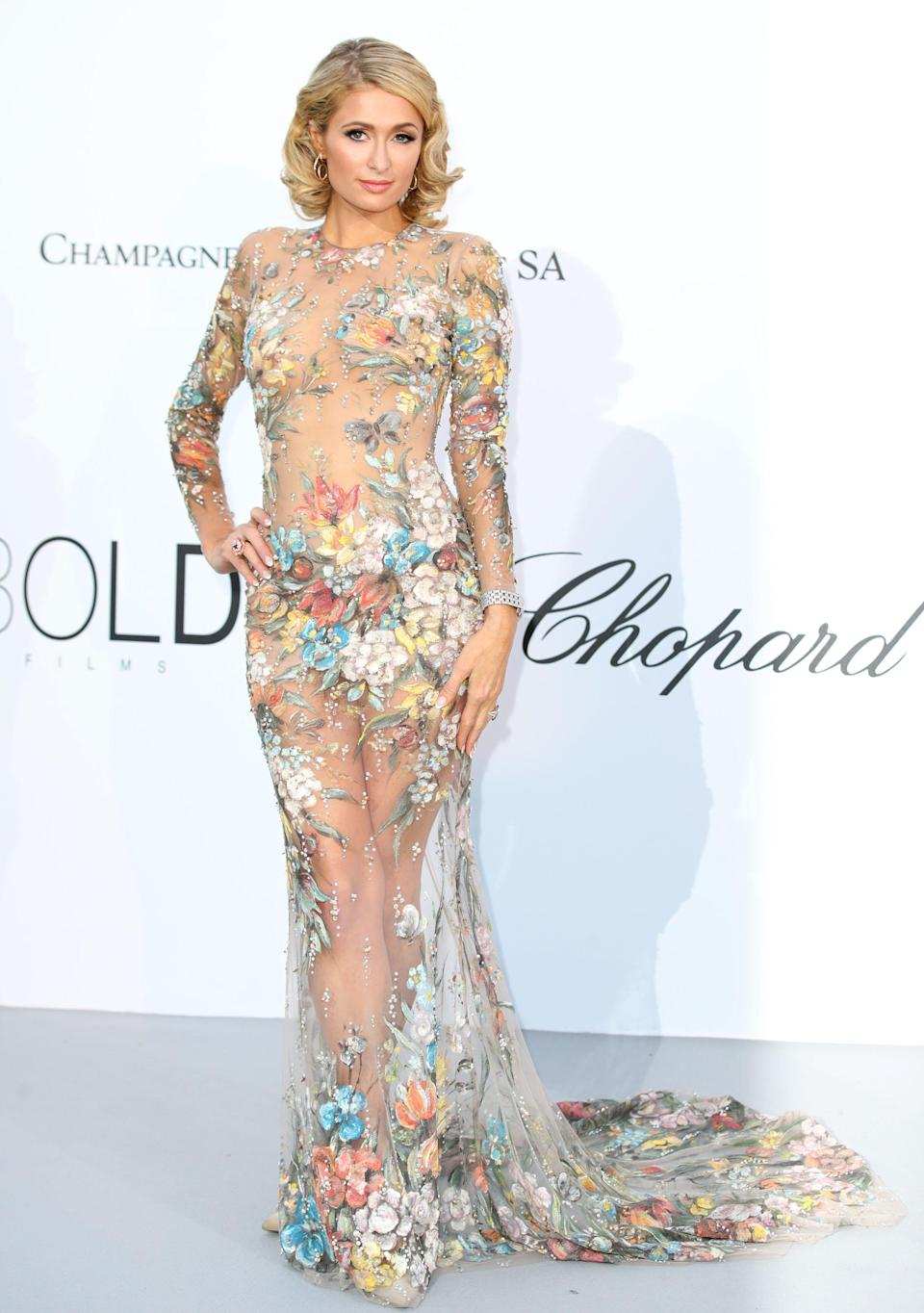 <p>Paris Hilton stole the sartorial spotlight in Cannes thanks to a sheer dress with strategically placed embroidered flowers. [Photo: Getty] </p>
