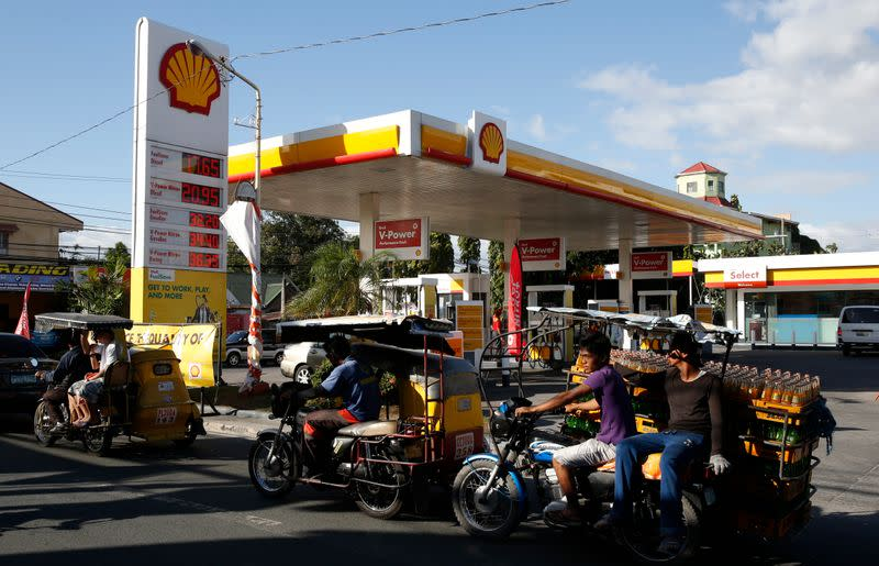 FILE PHOTO: Residents transport commuters and soda bottles on tricycles past a Shell petrol station in Las Pinas