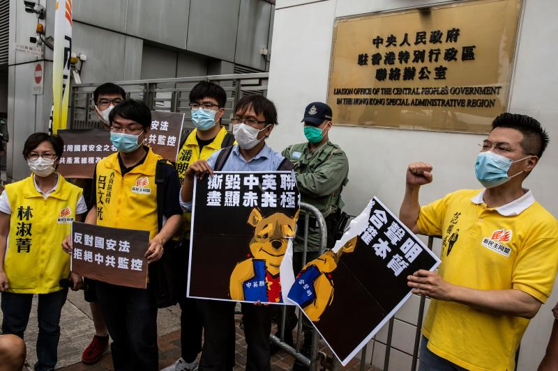 Pro-democracy activists tear a placard of Winnie-the-pooh that represents Chinese President Xi Jinping during a protest against a proposed new security law outside the Chinese Liaison Office in Hong Kong on May 24, 2020. - The proposed legislation is expected to ban treason, subversion and sedition, and follows repeated warnings from Beijing that it will no longer tolerate dissent in Hong Kong, which was shaken by months of massive, sometimes violent anti-government protests last year. (Photo by ISAAC LAWRENCE / AFP) (Photo by ISAAC LAWRENCE/AFP via Getty Images)